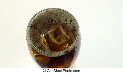 Coca Cola is poured into a glass from a bottle. White...