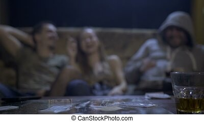 Cocaine and alcohol with addicts on background - Cocaine...