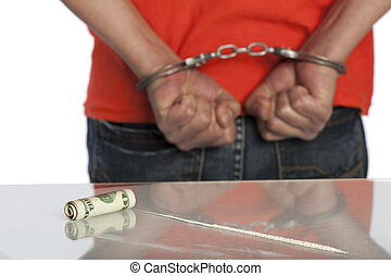 Cocaine arrest - Man in handcuffs next to a table with a...