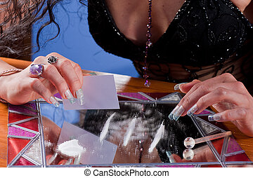 Cocaine - Woman preparing a line of cocaine on a fancy...