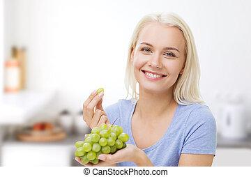 cocina, mujer que come, uvas, feliz