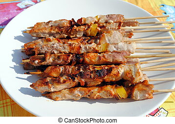 cocked pork kabobs grilled on skewers in a plate