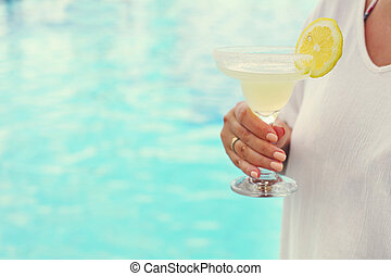 Cocktail glass in womans hand near the pool
