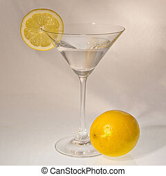 Cocktail glass with a lemon slice and a whole lemon in front
