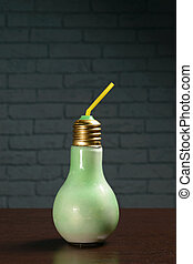 Cocktail in a green bulb glass on a wooden table