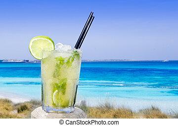 Cocktail mojito ice lemon straws in tropical beach balearic Islands