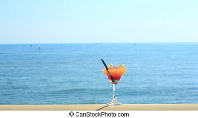 cocktail on beach, blue sea and sky background.