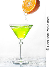 cocktail splash in glass isolated with an orange on a white back