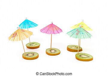 cocktail umbrellas on the slices of kiwi