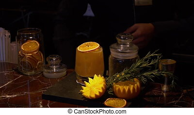Cocktail with a dry orange slice - A steady, medium shot of...