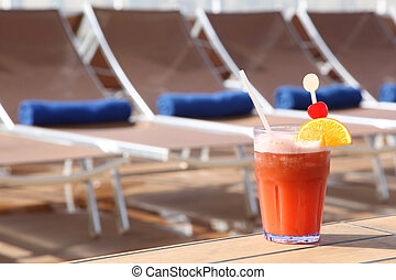 cocktail with fruits in glass on rail near beach armchair in...