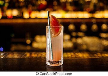 Cocktail with grapefruit on the wooden steel bar counter