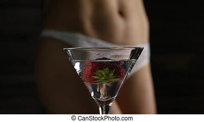cocktail with strawberry and blured female buttocks in white...