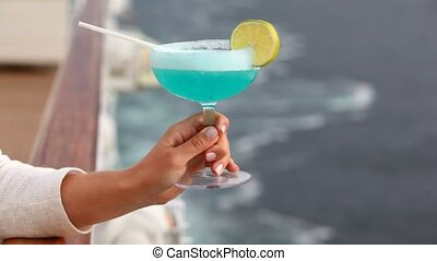 cocktail with straws and in hand lemon against handrail of ship