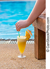 cocktail, woman's hand and view of the pool in the tropics