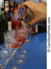 Cocktails - A bartender pours a line of cocktails