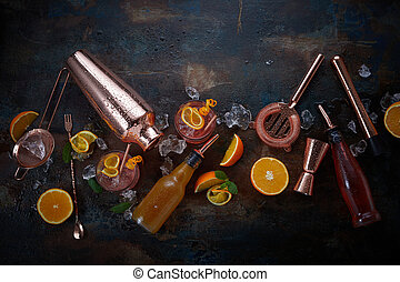 Cocktails or pub flat lay still life with copper bar equipment, chilled alcoholic beverages in glasses and sliced fresh oranges for garnishes scattered on a dark background
