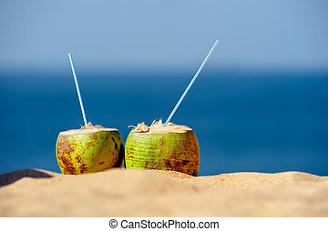 Coco Cocktail - Coconuts with drinking straw on the sand at...