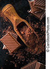 Cocoa and few pieces of chocolate with creamy filling