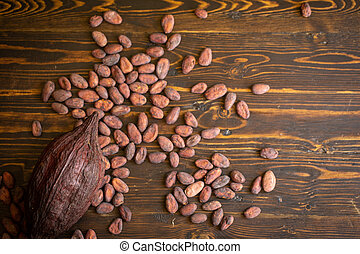 Cocoa beans and cocoa pod on old natural wooden background