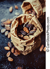 Cocoa beans in a paper bag on a dark background