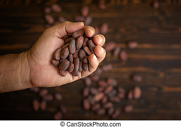 Cocoa beans in hand on old natural wooden background