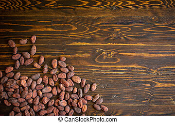 Cocoa beans on old natural wooden background