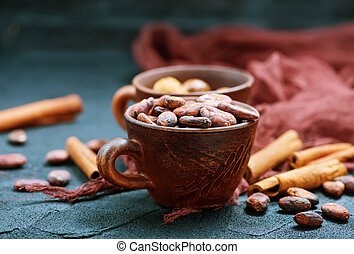 cocoa beans in cup and on a table
