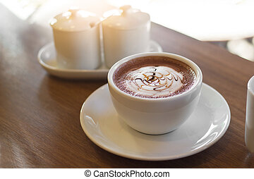 Cocoa drink in white cup on wooden background
