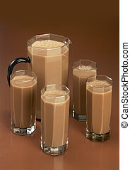 Cocoa drink in glases on brown background