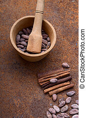 Cocoa flat lay  concept with raw cocoa beans in woooden bowl ,  twig of cinnamon on iron  background,