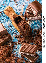 Cocoa in spoon and chocolate with creamy filling on blue board