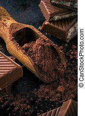 Cocoa in spoon and few pieces of chocolate