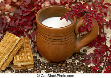 cocoa milk in a handmade stein surrounded by autumn plants of red color and waffles