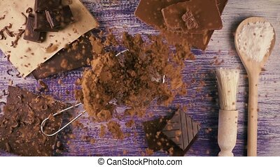 Cocoa powder falls on chocolate. Slow motion. Top view