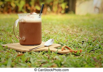 cocoa with a teaspoon on a background of green grass.