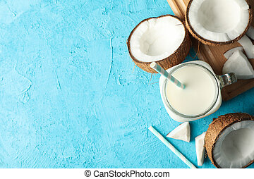 Coconut and milk on blue background, top view