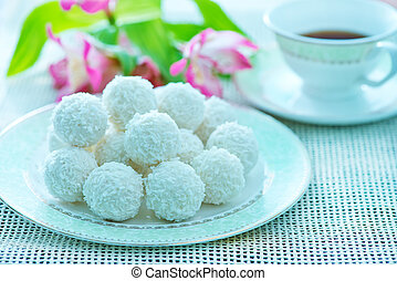coconut balls on the white plate and on a table