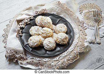 Coconut biscuits with icing sugar over pewter plate