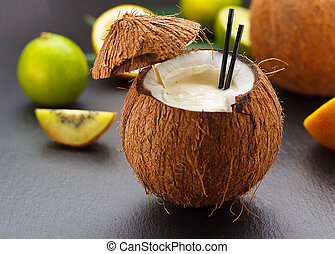 Coconut cocktail on a black table with kiwi, orange and lime.