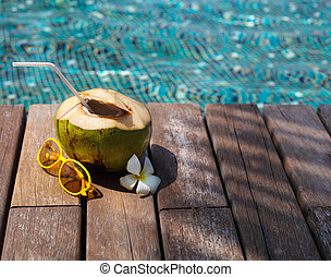 Coconut cocktail with drinking straw by the swimming pool -...