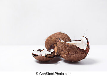 Coconut cracked in half on white background