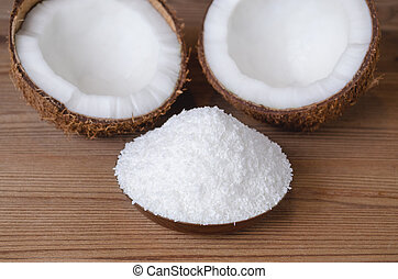 coconut flakes in a bowl on wooden background