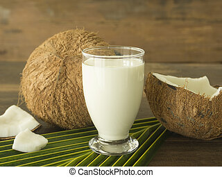 Coconut milk in a glass on a wooden table.