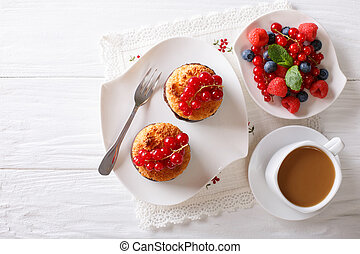Coconut muffins with berries and coffee with milk close-up on the table. Horizontal top view