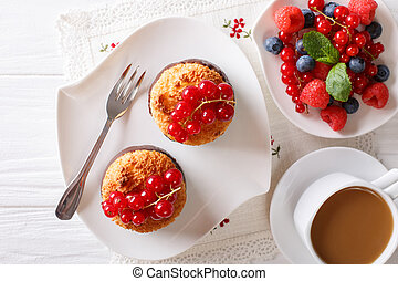 Coconut muffins with currants and coffee with milk close-up on the table. Horizontal top view