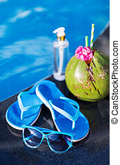 Coconut oil, drink, slippers, sunglasses, pool - summer health holiday concept