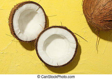Coconut on yellow background, top view. Tropical fruit