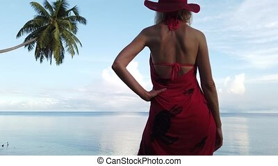 Blonde woman in red sarong on a shore - Coconut palm tree...