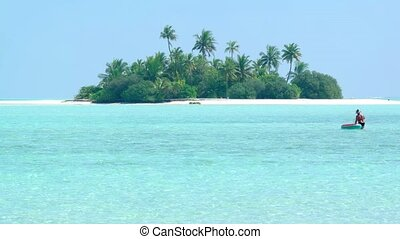 Coconut palms over a tiny, exotic island paradise with white...